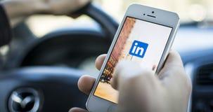 Facendo uso di Linkedin nell'automobile sul iphone Fotografie Stock Libere da Diritti