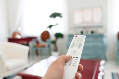 Facendo uso di telecomando bianco Programmi la commutazione o il bottone che preme sulla tastiera della TV Salone luminoso Casa d Immagine Stock Libera da Diritti