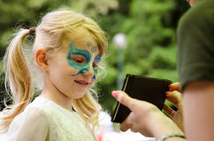 Facepainting. Girl with long blond hair with facepainting looking in mirror royalty free stock images