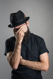 Facepalm of bearded hipster wearing black hat and t-shirt Stock Photo