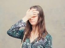 Facepalm-Mädchen auf grauem Wandhintergrund Lizenzfreie Stockfotos