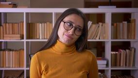 Facepalm moreno bonito de los gestos del profesor que cubre la cara con la mano que es molestada e irritada en la biblioteca metrajes