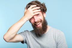 Facepalm som ler besvär för skam för manräkningsframsida arkivbilder