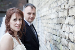Faces of bride and groom against brick wall Royalty Free Stock Photo