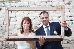 Faces of bride and groom in portrait frame Stock Photos