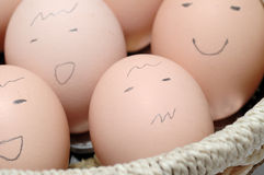 Faces drawn on eggs. Eggs in a basket with pencil faces Royalty Free Stock Photography