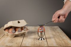 Faces on eggs. On wooden work top stock photos