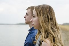Faces of the girl and the guy close-up in profile.A young couple stock image