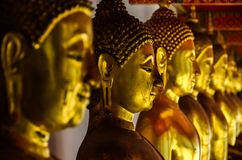 Faces of golden buddha statue in temple stock photos
