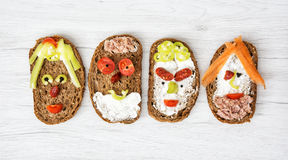 Faces made of bread, butter, tuna, sausage, carrot, paprika, bla Royalty Free Stock Photo