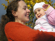 Faces mother with baby on autumn leaves. Smile faces mother with baby on autumn leaves royalty free stock photography