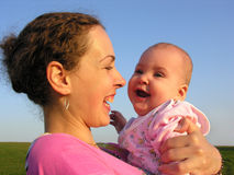 Faces mother with baby on sunset. Happy faces mother with baby on sunset on blue sky and green grass stock photo