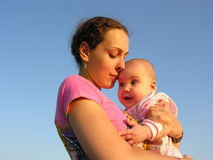Faces mother with baby on sunset touch nose. Blue sky stock image