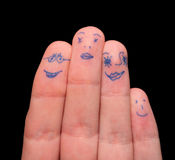 Faces painted on fingers. Isolated on black royalty free stock photo