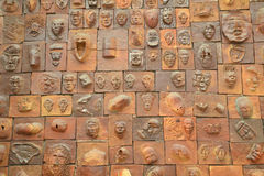 Faces. Sculpted faces on a wall in Fosan Stock Photo