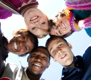 Faces of smiling Multi-racial college students. A group of smiling faces of multi-racial college students outside with the blue sky in the background royalty free stock images