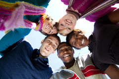 Faces of smiling Multi-racial college students. A group of smiling faces of multi-racial college students outside with the blue sky in the background stock image