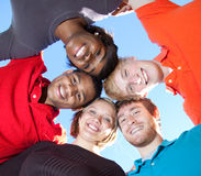 Faces of smiling Multi-racial college students. A group of smiling faces of multi-racial college students outside with the blue sky in the background stock photo