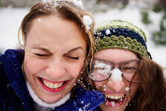 Faces of two young women are closed up with snow. Royalty Free Stock Photo