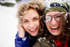 Faces of two young women are closed up with snow. Stock Images