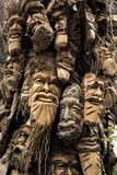 Faces. Wood carving human faces on bamboo tree stock images
