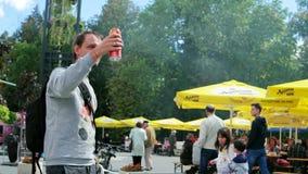 Facetów chwyty konserwują piwo, mężczyzna powitanie i dzwonić przyjaciel, uliczny karmowy festiwal zdjęcie wideo