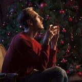 Facetów sen obsiadanie przy choinką na Bożenarodzeniowej nocy Fotografia Stock