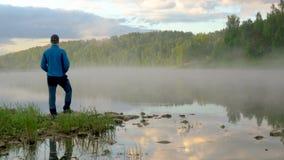 Facetów stojaki na banku na rzece i spojrzenia przy ranek mgłą zbiory wideo