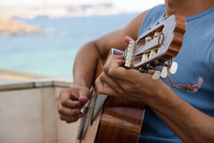Facet bawić się gitarę na balkonie na morzu Zdjęcie Royalty Free