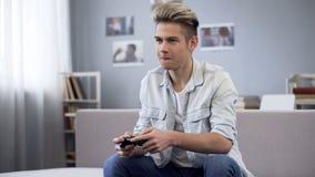 Facet bawić się grę komputerową z kontrolerem, martwiącym się o wygraniu, nałóg zdjęcia stock