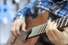 Facet bawić się klasyczną gitarę w muzycznym sklepie, muzykalny nastrój, muzyka klasyczna zdjęcie stock
