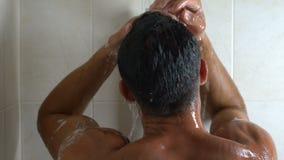 Facet bierze prysznic, cieszy się ciepłe krople na jego ciele, marnotrawny wodny spożycie zbiory