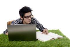 Facet czyta książkowego podczas gdy używać laptop na trawie Fotografia Stock