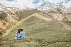 Facet dziewczyny przytulenia trawy lata duże góry śnieżne obraz royalty free