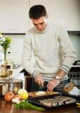 Facet gotuje surowej ryba z cebulą w prażak niecce obraz stock
