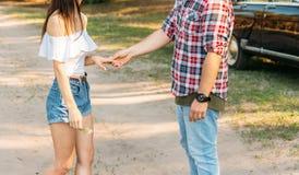 Facet iść, skromnie trzyma dziewczyny ręką, rozmowy, oferty małżeństwo w tle jest czarny samochód oferty obrazy royalty free
