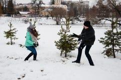 Facet i dziewczyna bawić się snowballs w miasto parku zdjęcie stock