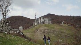 Facet i dziewczyna iść ręką antyczny kamienny forteca na zielonym wzgórzu zbiory