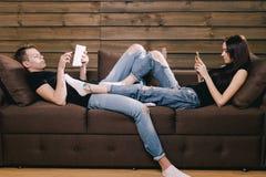 Facet i dziewczyna używa telefon i pastylkę fotografia stock