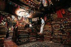Facet i dziewczyna wśród ogromnej liczby Orientalni dywany zdjęcia royalty free
