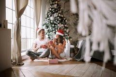 Facet i dziewczyna w białych Święty Mikołaj kapeluszach i koszulkach siedzimy z czerwonymi filiżankami na podłodze przed okno obo obrazy stock