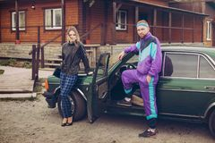 Facet i dziewczyna w ubraniach lata dziewięćdziesiąte obok starego samochodu, Zdjęcie Royalty Free