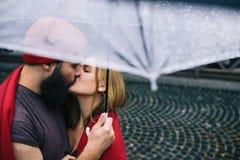 Facet i dziewczyny całowanie pod parasolem Zdjęcia Stock