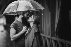 Facet i dziewczyny całowanie pod parasolem Fotografia Royalty Free