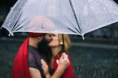 Facet i dziewczyny całowanie pod parasolem Zdjęcie Royalty Free