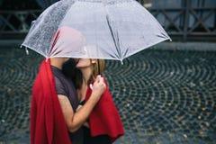 Facet i dziewczyny całowanie pod parasolem Obraz Royalty Free