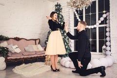 Facet jest na jego kolanie i trzyma pierścionek zaręczynowego w jego ręce Oferta dostawać zamężny w Bożenarodzeniowym czasie zdjęcie royalty free