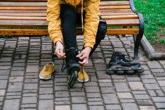 Facet jest ubranym rolkowe łyżwy w parku na ławce Zdjęcie Stock