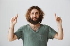 Facet no jest pewny że lubi co widzii Portret atrakcyjny arabski z długim kędzierzawym włosy i brodą wskazuje up zdjęcie stock