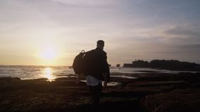 Facet otwiera jego ręki szerokie przeciw pięknemu złocistemu zmierzchowi na plaży, wyraża sens wolność, happines zbiory